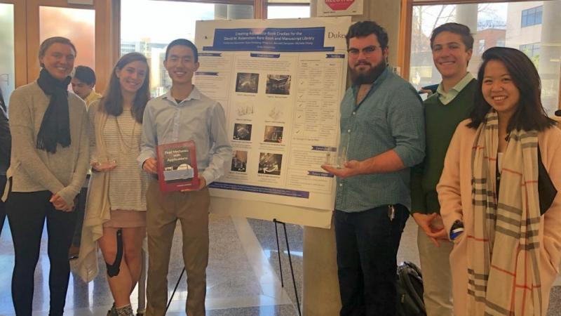 Book Cradle Team members hold prototype in front of poster.